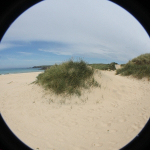 """""""Fisheye"""" view of a sand dune on Eoropaidh beach, with the rocky cliffs in the background."""