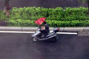Riding a Moped with an Umbrella
