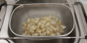Draining the cooked potatoes.