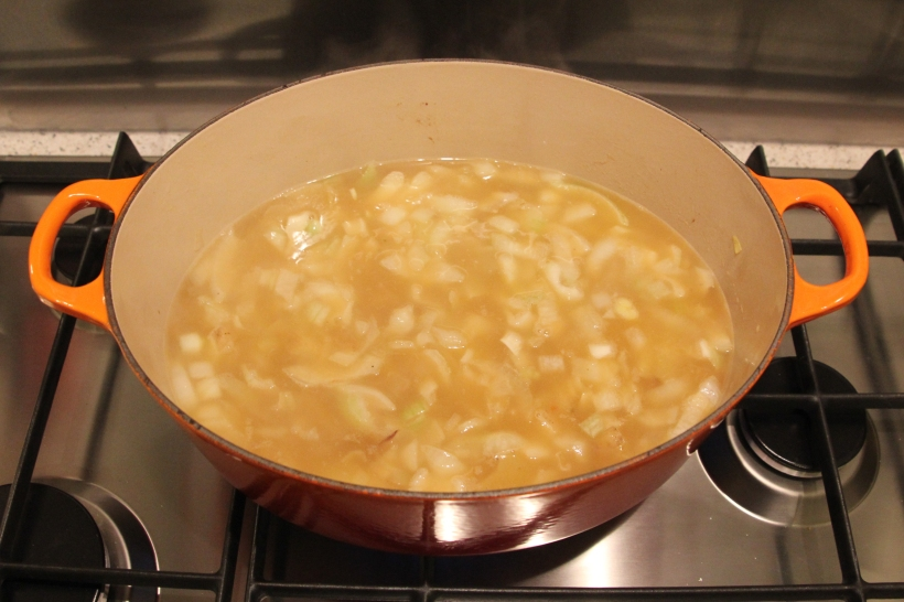 Stock added to onions and potatoes