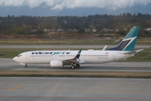 C-FUCS WestJet Boeing 737-800 taxiing west to takeoff on 26L, past gate 64.